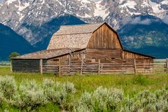 Old barn in Grand Teton Mountains. Old mormon barn in Grand Teton Mountains with low clouds. Grand Teton National Park, Wyoming, USA Royalty Free Stock Photography