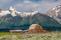 Old barn in Grand Teton Mountains. Old mormon barn in Grand Teton Mountains with low clouds. Grand Teton National Park, Wyoming, USA Royalty Free Stock Images