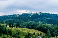 Old house and a barn on a meadow in the mountains. Old barn on a green meadow, Eastern Europe. Wooden houses and sheds, green meadows and forests are a typical royalty free stock photography