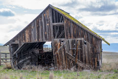 Old Barn with hidden treasures ready to collapse. Long abandoned homestead  barn is just about ready to collapse.  Hidden inside is an old horse drawn grain Royalty Free Stock Photos