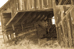 Old Barn with hidden treasures ready to collapse 2. Long abandoned homestead  barn is just about ready to collapse.  Hidden inside is an old horse drawn grain Royalty Free Stock Photo