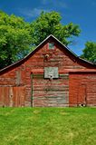 Old Barn Home to Outdoor Basketball. An old red barn supports a backboard, rim, net where a basketball game can be played Stock Photos