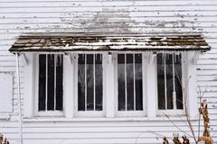 Old Barn ir shed with weathered wood on Farm. Agriculture Farm in the midwest America with  wood fading windows and icicles in winter with white painted siding Royalty Free Stock Photography