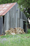 Old barn missing planks  faded by time, and time rusted tin roof Stock Image