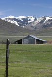 Old barn with mountain background. Old gray barn with barbed wire fence in foreground and snow covered mountains in distance Stock Photo