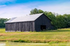 Old barn near pond. Country landscape Royalty Free Stock Image