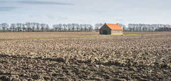 Old barn in a plowed field Stock Photo