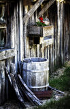 Old Barn with Rain Barrel and Geranium Stock Photo