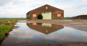 Old barn reflected in a puddle of water Royalty Free Stock Image