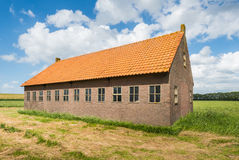Old barn in a rural landscape with a blue sky and white clouds. Royalty Free Stock Photo
