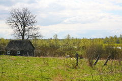 Old barn scene in western Russia.  rustic old farm building. old rustic barn. Pskov oblast, Northwest part of Russia, Europe. Aging cart near wooden barn. View Royalty Free Stock Photo