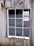 Old Barn or shed with weathered wood on Farm. Agriculture Farm in the midwest Ameriica with  wood fading windows and icicles in winter with white painted siding Royalty Free Stock Image