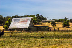 Old Barn & Sheds With American Flag On Roof. Old Barn & Sheds On Ranch With Faded American Flag On Barn Roof Stock Image