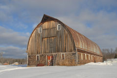 Old barn in snow. Cordwood barn in the snow against a cloudy blue sky Stock Image