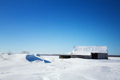 Old barn and snow drifts, Canada Stock Images