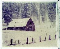 Old barn in snow storm. Polaroid image transfer on a cold press watercolor paper (rough texture Stock Photo