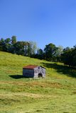 An old barn stands in the middle of a farm. Onm a sunny summer day Royalty Free Stock Image