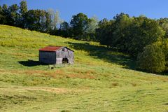 An old barn stands in the middle of a farm. Onm a sunny summer day Royalty Free Stock Photo