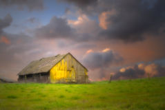 Old barn under dark skies with soft focus. Old rustic barn in a field under dark skies with soft focus and dramatic lighting Stock Images