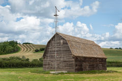 Old barn with a weather vane. Against a green farm field Royalty Free Stock Image