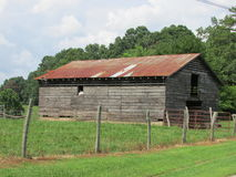 Weathered Old Barn with Rusted Metal Roof Stock Photography