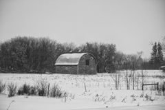 An old barn in a winter landscape. An old barn in a countryside winter landscape in black and white Royalty Free Stock Image