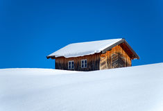 Old barn in winter. An old barn in winter. Photo taken in Austrian Alps (Galtür). Plain blue sky in the background royalty free stock photography