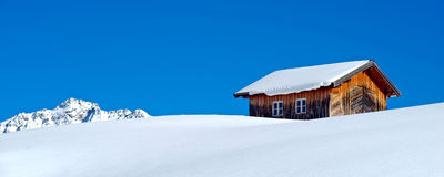 Old barn in winter. An old barn in winter. Photo taken in Austrian Alps (Galtür). Plain blue sky in the background and a piece of a mountain. Panoramic format royalty free stock photography