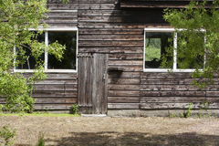 Old barn. Old wooden barn with big windows and a very small door Royalty Free Stock Photo