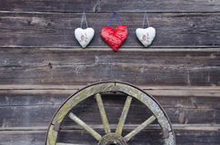 Old barn wooden wall with hearts and carriage wheel Royalty Free Stock Photo
