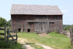 Old barn. In a yard with well-kept grass and old fencing Royalty Free Stock Images