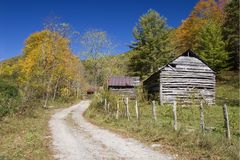Old Barns. In the Autumn Season with Blue Sky and dirt road stock images