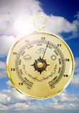 Old Barometer. Barometer with cloudy sky in the background royalty free stock image
