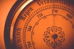 Old barometer dial close up with added orange filter. Old barometer dial close-up with added orange filter stock image
