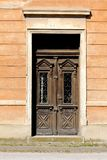 Old baroque style wooden front entrance doors with clear glass and metal decorative protective bars mounted on dilapidated family. House wall on warm sunny royalty free stock photos