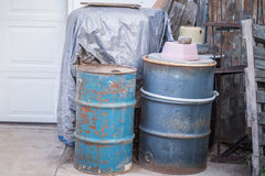 Old Barrels and Junk. Barrels, pallets, and other junk near a residential home Stock Photos