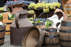 Old barrels and tools for wine production and  baskets with grapes Stock Photography