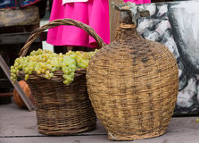 Old barrels and tools for wine production and baskets with grapes.  royalty free stock images