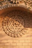 Hindu six-pointed star, and blooming flower in a centre. Old bas-relief on a temple wall - a Hindu six-pointed star, and blooming flower in a centre of stock image