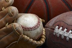 Old baseball. Close up shot of well worn baseball in baseball glove, football and basketball Stock Image