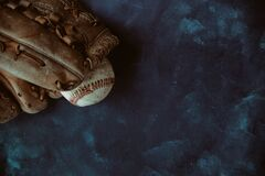 Old baseball background with ball in glove close up