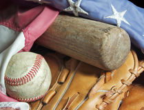 Old baseball bat, mitt, ball and flag. An old baseball bat, mitt and baseball sit nestled in an American flag Stock Images