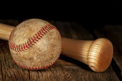 Old baseball and Bat. An old worn baseball and wood bat on wood surface with black background