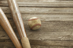 Old baseball and bats on rough wood surface Royalty Free Stock Photo