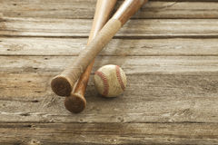 Old baseball and bats on rough wood surface Royalty Free Stock Photos