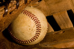 Old baseball and glove. Old worn baseball sitting in ragged glove in a closeup view Royalty Free Stock Photos