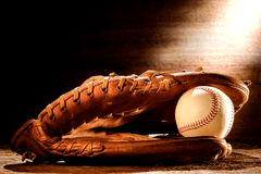 Old Baseball Glove and Ball in Nostalgic Light. Old worn leather baseball catcher sport glove and aged stitched ball on antique wood boards in soft nostalgic royalty free stock photo