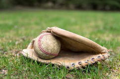 Old Baseball Glove and Ball. An old vintage baseball glove and ball lay on the early spring outfield Royalty Free Stock Photo