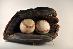Old Baseball Glove With Baseballs. Closeup of an old,worn ball glove with old baseballs Royalty Free Stock Image