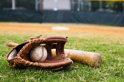 Old Baseball, Glove, and Bat on Field. With base and outfield in background Stock Photo